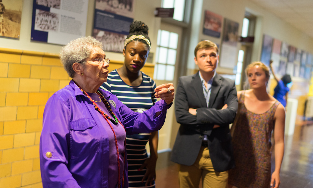 Photo of former Simms student presenting to JMU students in front of exhibit