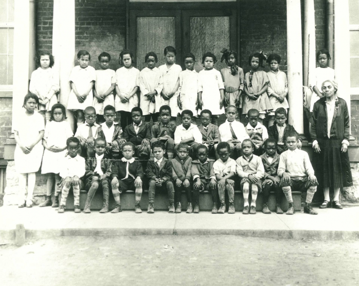 Black and white class photo of 33 elementary school students and Lucy Simms on the front steps of the school building.