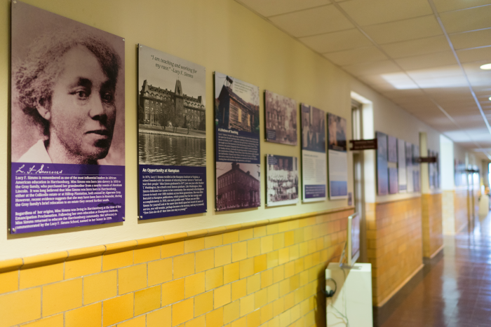 Lucy Simms exhibit containing black and white photos and panels on the wall of the former school.