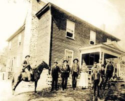 Black and white photo of family in front of house.