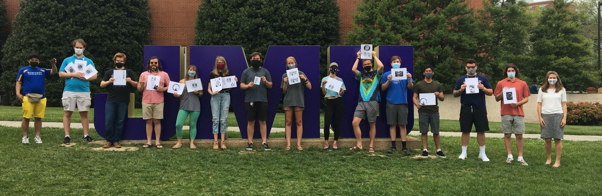 group photo of 14 students and professor holding up papers with images printed on them