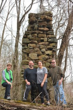 Photo of modern day Hawkins family standing in front of stone chimney in the woods