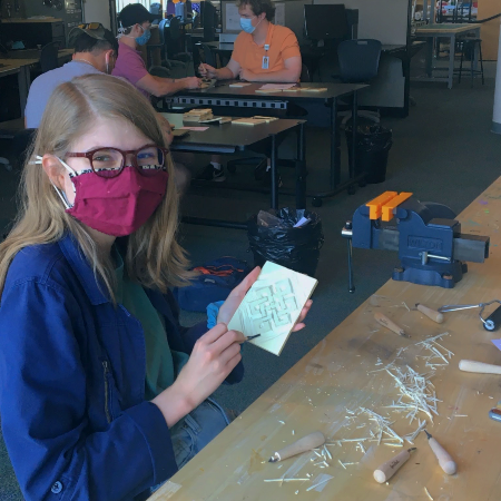 student holding linoleum block and carving tool