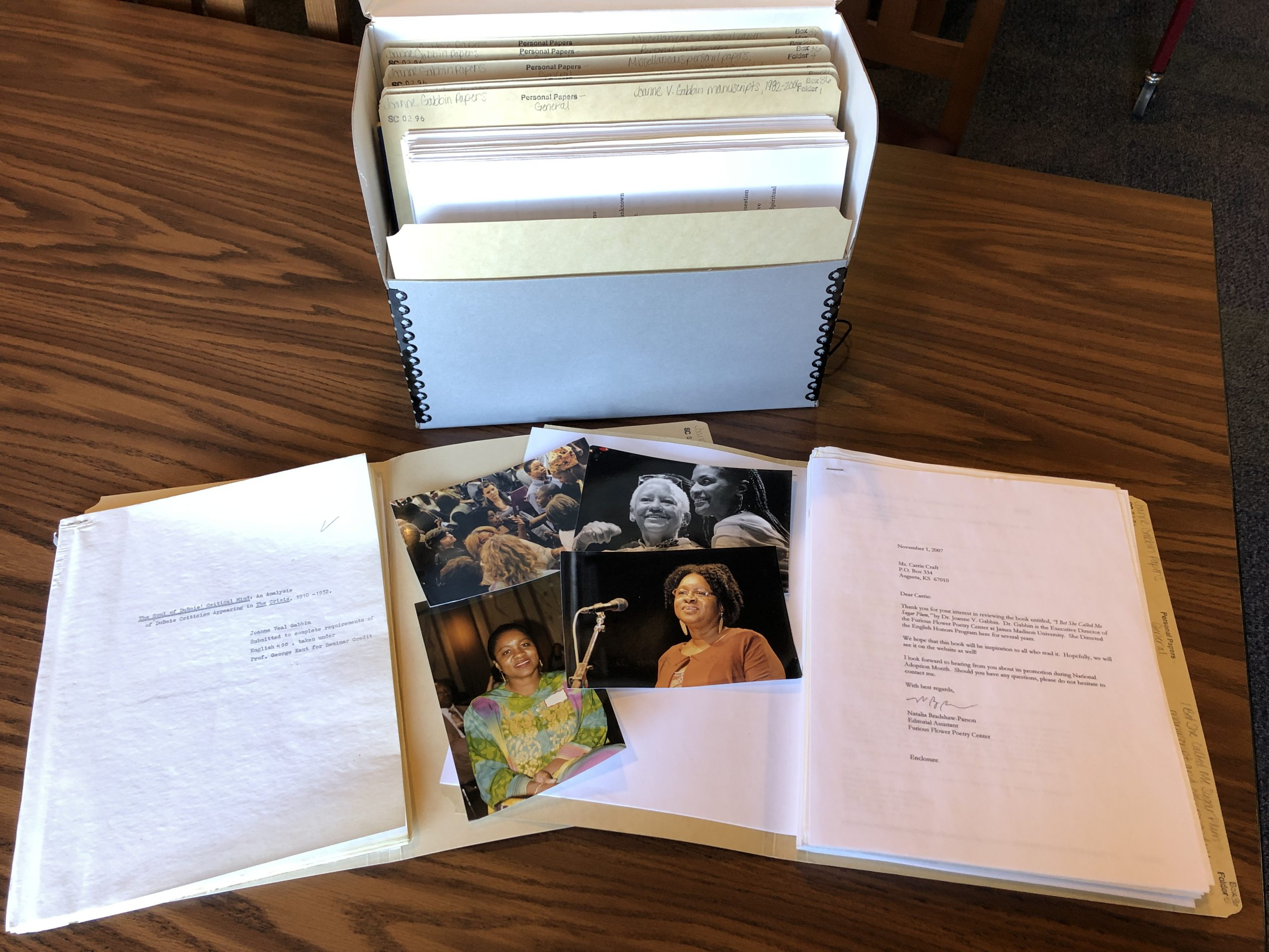 Letters and photos in front of a box of documents.